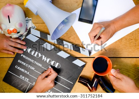 Two directors working in team. The following objects are organized on the wooden table: smart phone, movie clapper, rapid access film. - stock photo