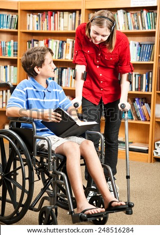 Two disabled kids in the school library, one in a wheelchair and one with crutches.   - stock photo