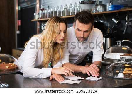 Two disappointment cafe owners calculating revenue - stock photo