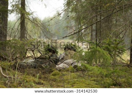 Two disguised soldiers watching the movement of the enemy  - stock photo