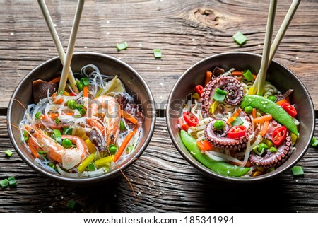 Two dishes with vegetables, noodles and seafood - stock photo