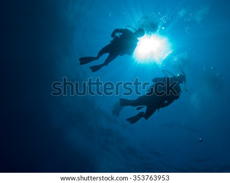 Two divers in silhouette descending at the begining of a dive, looking up with sun burst