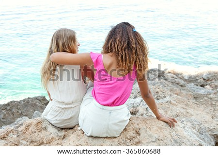 Two diverse friends, caucasian and african american teenager girls sitting together on rocks smiling, relaxing contemplating the blue sea, outdoors nature. Holiday travel lifestyle, beach exterior. - stock photo