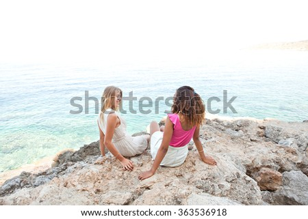 Two diverse friends, caucasian and african american teenager girls sitting together on textured rocks smiling, relaxing by the blue sea, outdoors nature. Healthy well being holiday travel lifestyle. - stock photo