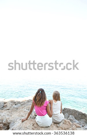 Two diverse friends, caucasian and african american teenager girls together on rocks, relaxing and contemplating the blue sea, outdoors nature. Healthy well being holiday lifestyle, beach exterior. - stock photo