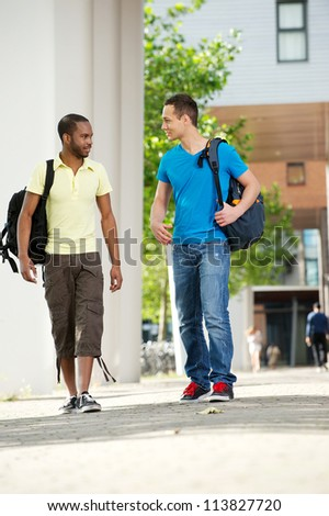 Two diverse students walking. Full length portrait of African American and Caucasian students wearing bags and talking to each other. - stock photo