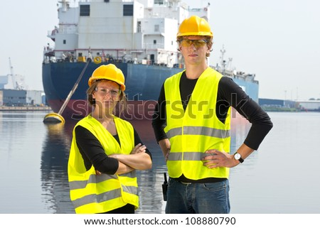 Two dockers, a man and a woman, posing in front of a huge cargo ship, moored off at an anchor buoy in an industrial harbor - stock photo