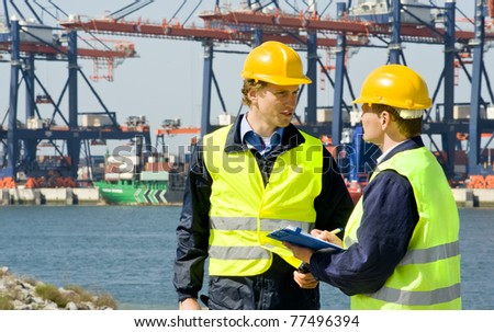 Two dockers at work in a big container harbor - stock photo