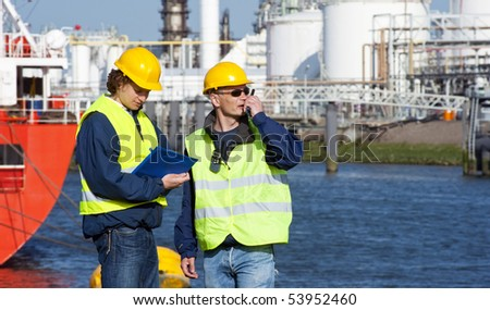 Two dockers during a routine inspection of an industrial harbor - stock photo
