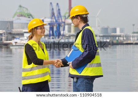 Two dockers greeting eachother in an industrial harbor, wearing the necessary safety gear - stock photo