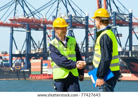 Two dockers shake hands in front of an industrial harbor with cranes and a container ship being unloaded - stock photo