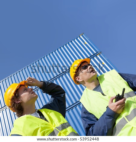 Two dockers, wearing a hard hat and safety vests at work under a blue sky, with huge containers in the background. - stock photo