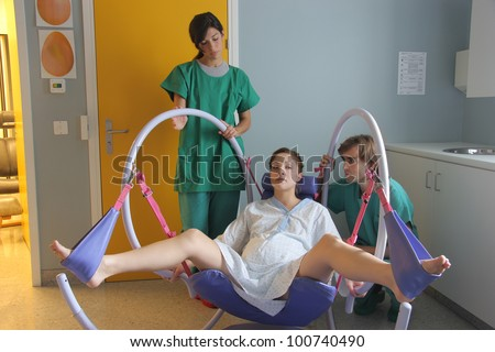 Two doctors and a pregnant woman in a delivery room - stock photo