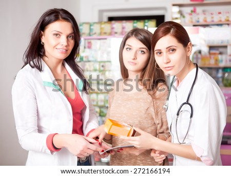 Two doctors and one client inside pharmacy. The medics are consulting the client. Customer care. Healtcare business - stock photo