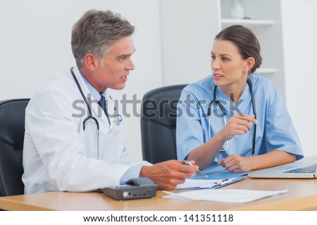 Two doctors discussing and working together in a medical office - stock photo