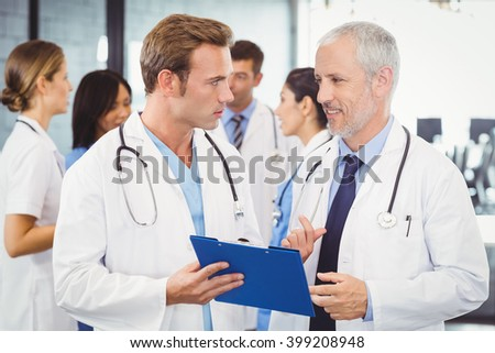 Two doctors looking at clipboard and discussing in hospital - stock photo