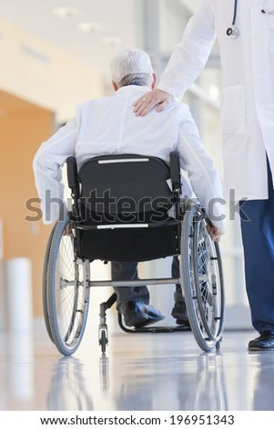 Two doctors, one in a wheelchair, walking in a hospital corridor.