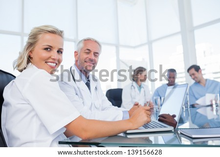 Two doctors smiling and looking at the camera - stock photo