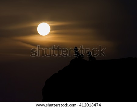 Two dogs silhouette on cliff with blurred moon view from highland