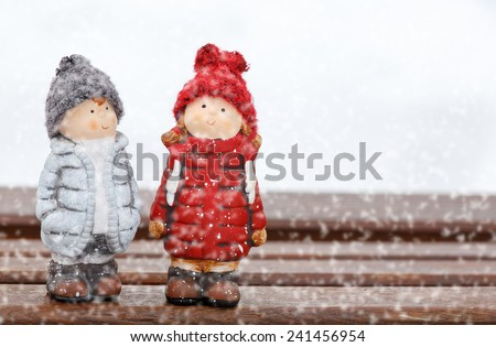 two dolls stand on desk at winter day, snowing - stock photo