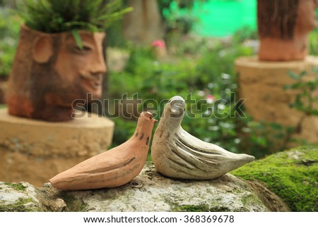 Two doves ceramic sitting on a rock - stock photo