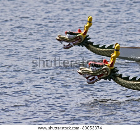 Two dragon boats race neck and neck (with focus on foreground boat). - stock photo