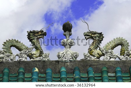 Two dragons atop a temple entrance in Hong Kong - stock photo
