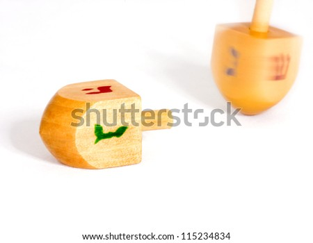 Two dreidels, one fallen, the other spinning, shown isolated on a white background. Dreidle is a traditional game for the Jewish holiday of Chanukah. - stock photo