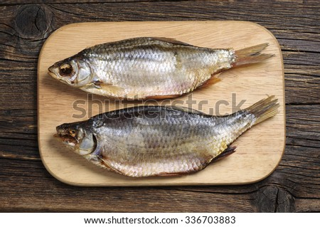 Two dried fish on a cutting board, top view
