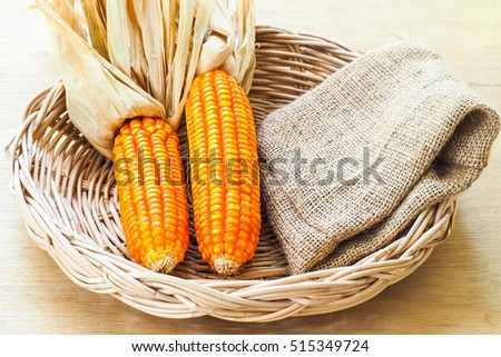 Two dry corn in a bamboo basket with Sack bag.