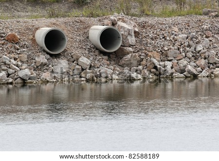 two dry pipes on waterside pointed to the river - stock photo