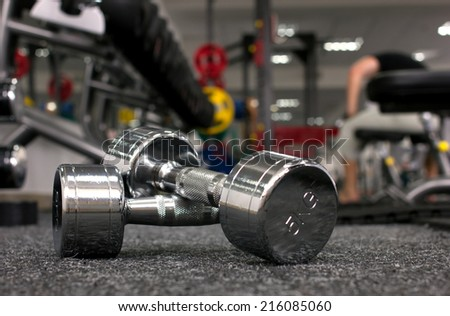 Two dumbbells in gymnasium on blurred background - stock photo
