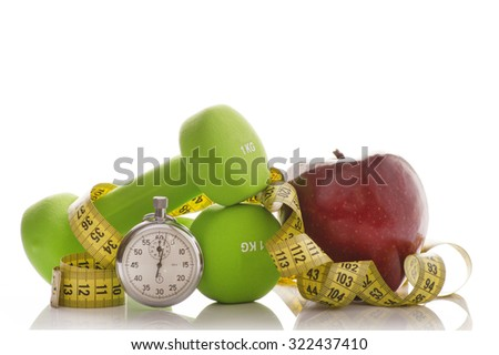 Two dumbbells, red apple, measuring tape and a stopwatch isolated on white background. Diet concept. Equipment for fitness and healthy eating - stock photo