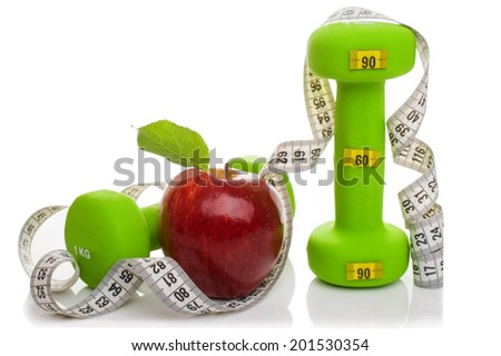 Two dumbbells, red apple, measuring tape isolated on white background. Diet concept. - stock photo