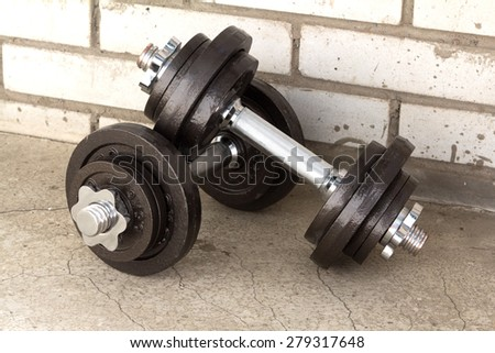 two dumbbells standing on concrete floor