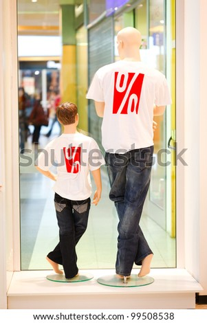 Two dummies in symbolizing discount shirts shot from behind - stock photo