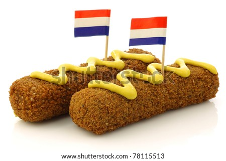 "Two Dutch snacks called ""kroket"" with mustard and  Dutch flag toothpicks on a white background - stock photo"