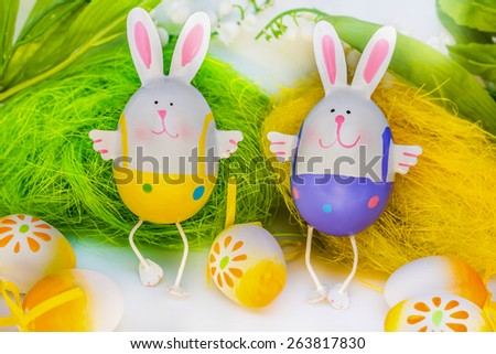 Two Easter bunnies against green and yellow background - stock photo