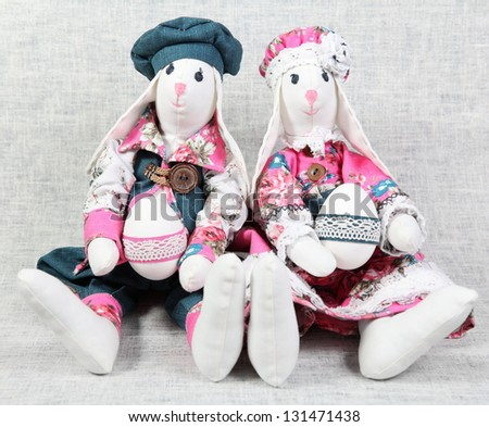 Two Easter Bunnies Holding Colorful Decorated Eggs