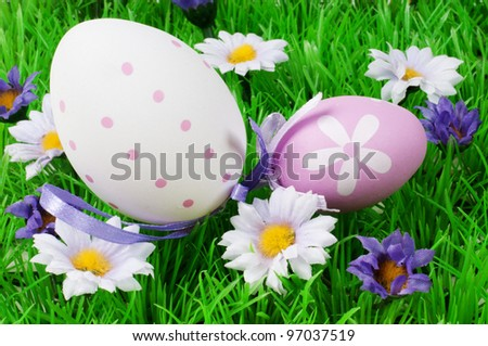 Two Easter eggs on a field with flowers