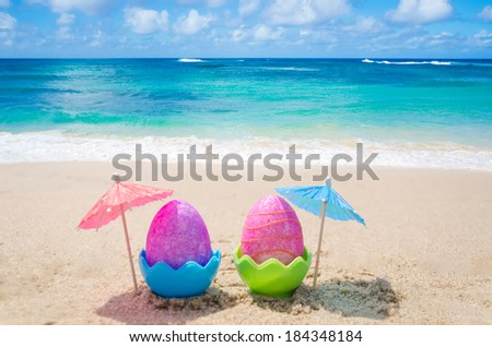 Two easter eggs with cocktail umbrella on the sandy beach - stock photo