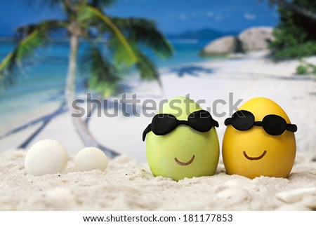 Two easter eggs with sunglasses on ocean beach
