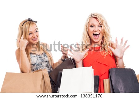 Two ecstatic blond girls shopping, isolated on white background - stock photo