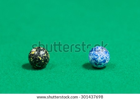Two Egg like black and blue Colorful Marble Balls on Green background - stock photo