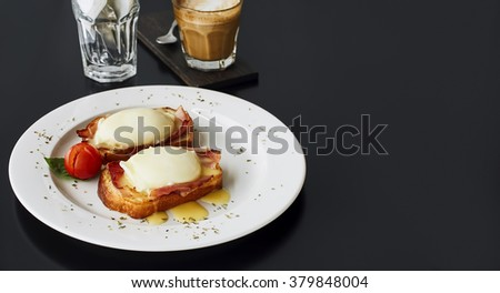 Two eggs benedict on white plate