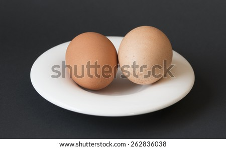 Two eggs in saucer on black setting - stock photo