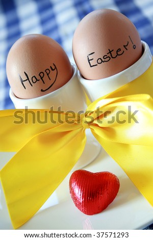Two eggs in white egg cups with an Easter message - stock photo