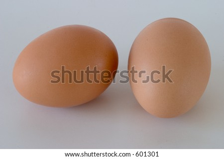 Two eggs sitting on the counter, side by side, close-up.