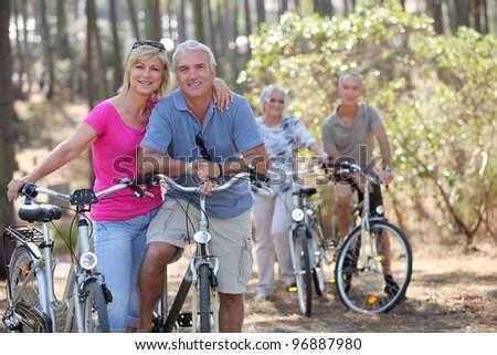Two elderly couples on bike ride - stock photo