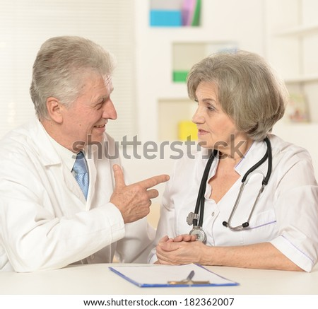 Two elderly doctors talking at the table